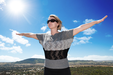 Woman spreding arms under the sun Standard-Bild