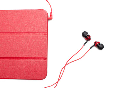 Red tablet and earphone plugs isolated on a white background Standard-Bild