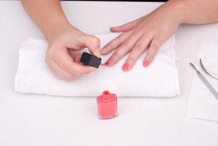 Female putting colour nail polish on her hand Standard-Bild