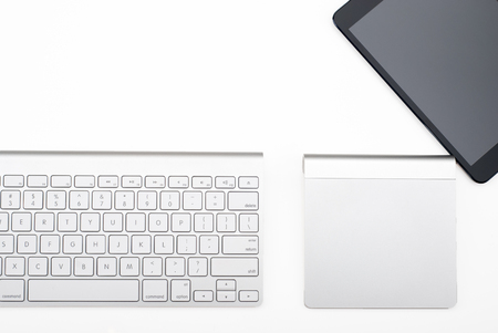 Keyboard, trackpad and tablet viewed from above isolated on a white background