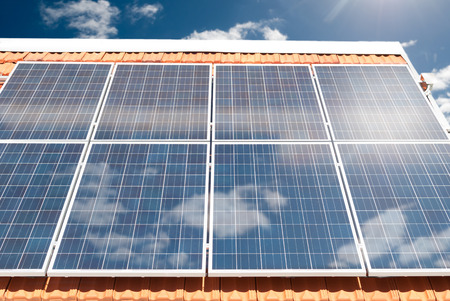 Solar (photovoltaic) panels producing electricity on a house roof during a sunny day