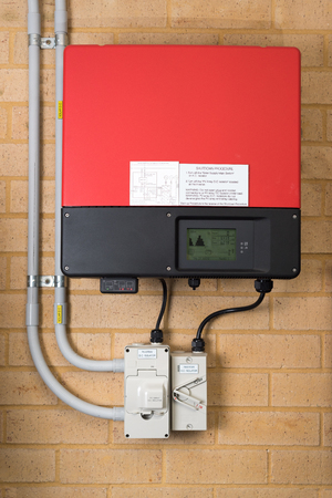 Red inverter system attached to a brick wall