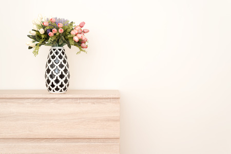 Flowers in a white and black vase positioned on a wooden drawer. Copy space on white background available.