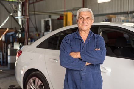 Caucasian mechanic with white hair servicing a car in an automative workshop
