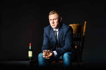 Portrait of serious elegant handsome young man in classic suit toasting with glass of alcohol on black background.