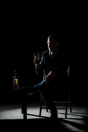 man in suite: Brutal man drinking whiskey black background in classical suite