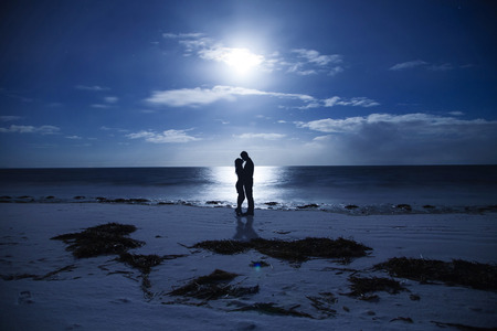 Silhouette kissing couples night at the seaside