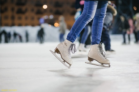winterday: the girl on the figured skates on a skating rink