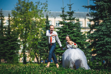 weddingrings: happy bride and groom running on the green grass