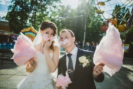 pareja comiendo: a pie de recién casados ??en el parque de diversiones con algodón de azúcar Foto de archivo