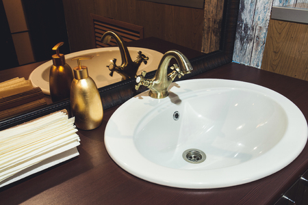 bronze faucet in the bathroom washstand paper towels