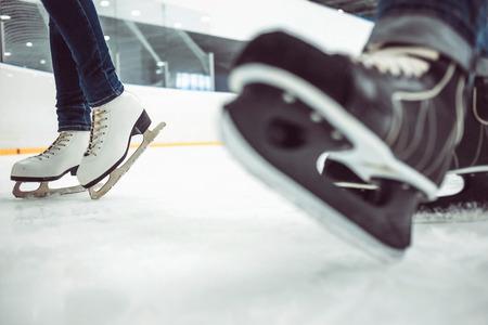 Man's hockey skates on ice backgroundMan's hockey skates and women's figure skates on ice background. 免版税图像