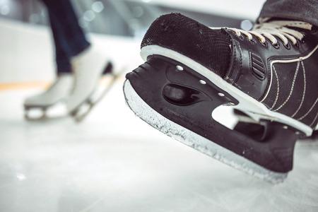 edge of the ice: Mans hockey skates on ice backgroundMans hockey skates and womens figure skates on ice background.