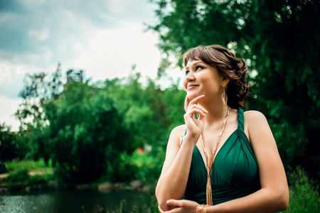 decollete: Portrait of a young attractive smiling girl in green dress with deep decollete  in the park
