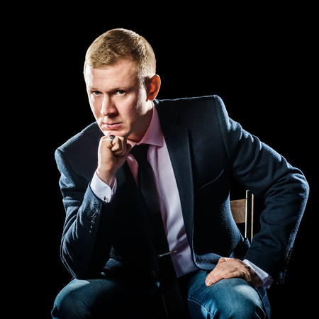 exacting: Portrait of serious elegant handsome young man in classic suit toasting with ring on black background. Stock Photo