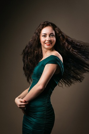 healthful: beautiful healthful curved girl waved her curly hair in studio