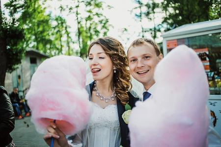 pareja comiendo: feliz pareja de recién casados ??divertido caminar en el parque de diversiones con algodón de azúcar.