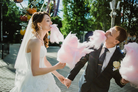newlywed: newlywed happy funny couple walking in the amusement park with cotton candy.