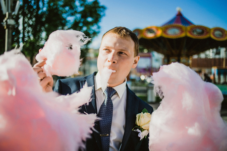 cotton candy: newlywed happy funny couple walking in the amusement park with cotton candy.