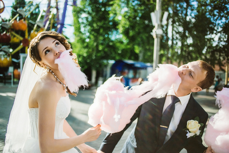 wedding bride: newlywed happy funny couple walking in the amusement park with cotton candy.
