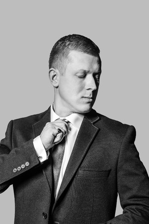 exacting: Well dressed business man adjusting his  tie.  Monochrome photo isolated grey background.