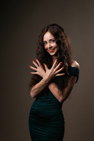 healthful: brunette girl  with curly long hair shows beautiful hands with long fingers and fashionable design of healthful red nails on dark  background.