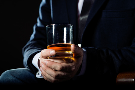 whiskey glass: Closeup of serious businessman holding  whiskey to illustrate executive privilege concept