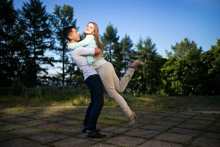 parejas romanticas: Hombre alegre muchacha levantando en el parque de la mañana.