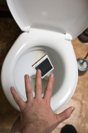 Closeup picture of mans hand  throws broken phone in toilet