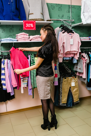 children clothing: Young mother buys clothes for little child in childrens clothing store.