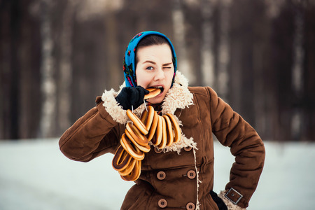 attractive charismatic: Young  charismatic attractive  woman clothed sheepskin coat and scarf. Girlthe bites off the bagel. Spring time.