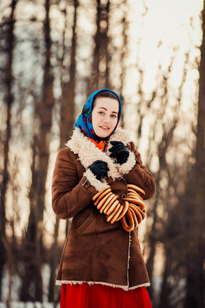 clothed: Young  charismatic attractive  woman clothed sheepskin coat and scarf. Girl holding the bagels. Spring time.