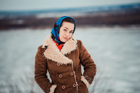 attractive charismatic: Young  charismatic attractive  woman clothed sheepskin coat and scarf. Girl looks at camera near big river. Spring time.