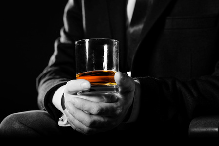 Closeup of serious businessman holding whiskey illustrate executive privilege concept. Monochrome photo. ?olor emphasis on a glass of whisky