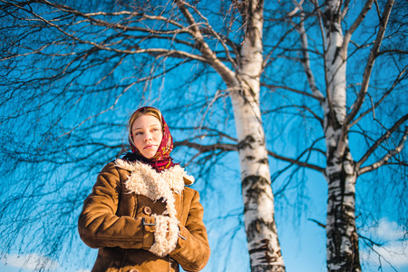 sheepskin: Beautiful blond woman in russian winter suit stay near the birch and thoughtfully looks afar. Girl clothed scarf, sheepskin coat. Stock Photo