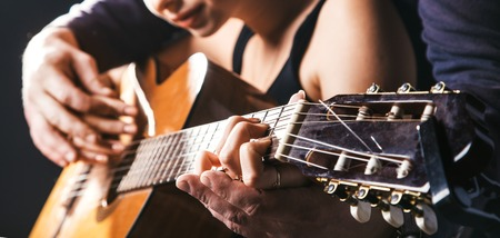 blurred man's hands playing acoustic guitar, and teaching guitar, too softa girl to play guitar. Black concert studio background.