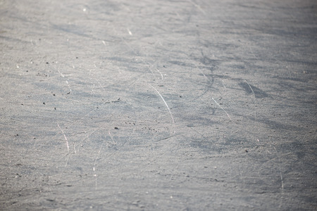 cracks in ice: Bad ice at the city rink in sunny spring day. Many bands, cuts, cracks. Stock Photo