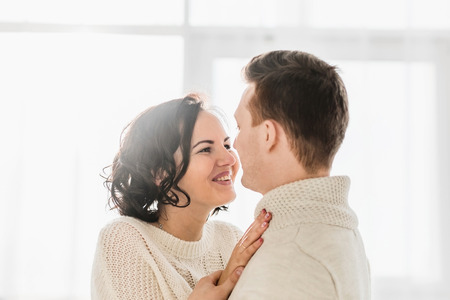 Romantic couple in light room staring at each others eyes. Stock Photo