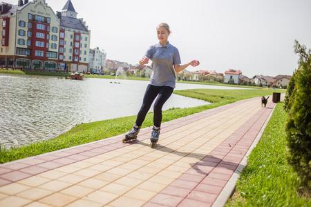 rollerskating: Beautiful teenage girl rollerskating in summer park.