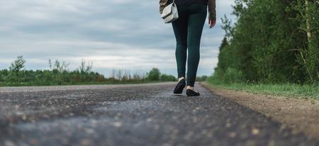 Die Beine der jungen Frau in Freizeitkleidung zu Fuß die Waldstraße. Konzept der Einsamkeit, Unsicherheit, Wahl.