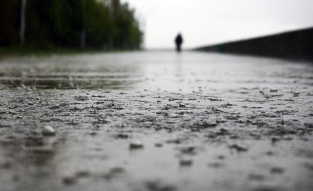 selective focus: Heavy rain in the city with silhouette of alone man. Concept of loneliness, bad weather Stock Photo