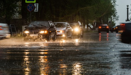 torrential: Heavy rain hitting a concrete sidewalk while cars drive by. Selective focus Stock Photo