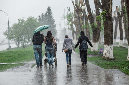 Group of people walking down the street at heavy rain in motion blur. Concept of bad weather, resistance to difficulties 免版税图像