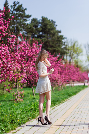 Beautiful blonde girl with long wavy curls in a beautiful white dress walk in the park among the pink trees, stunning makeup.