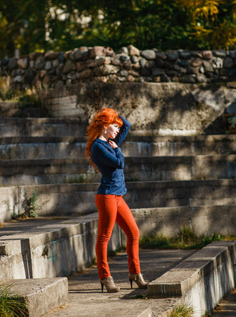 red pants: Beautiful young redhead woman smiling and holding her hands in her hair with hear eyes. Girl clothed in blue skirt, red pants. Autumn fashion concept. Stock Photo