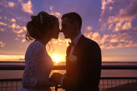 Harmonious beautiful bride and groom holding hands look at each others eyes at colorful sunset on the observation deck. Stock Photo