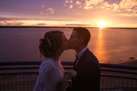 harmonious: Harmonious beautiful bride and groom holding kissing at colorful magenta sunset on the observation deck