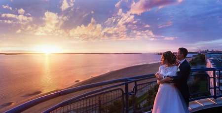 magenta dress: A panoramic view on a wedding couple standing on the roof and watching the sunset.