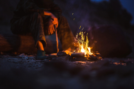 woodfire: Person warms their feet next to a campfire at dusk camping in the woods.