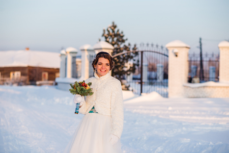 chuckle: happy and beautiful bride smiles and holds bouquet of orange roses at winter outdoors. Stock Photo